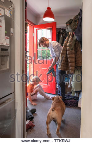 Father assisting son in getting dressed at doorway - Stock Photo