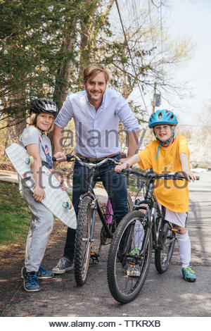 Portrait of happy father and sons with bicycles and skateboard standing on road - Stock Photo