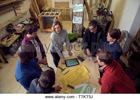 High angle view of businesswoman explaining to colleagues over tablet computer in workshop - Stock Photo