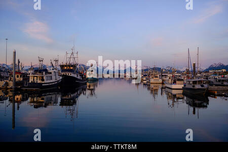 Boats moored in lake against snowcapped mountain during sunset - Stock Photo