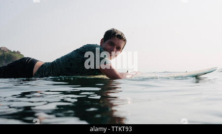 Side view portrait of smiling young man lying on surfboard in sea against sky - Stock Photo