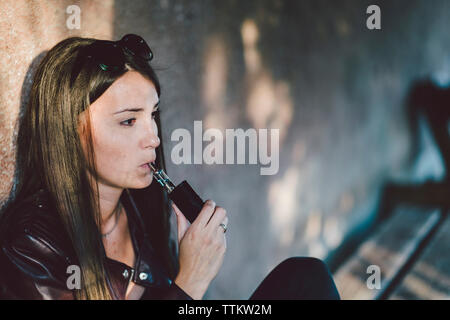 Young woman smoking electronic cigarette while sitting against wall on footpath - Stock Photo