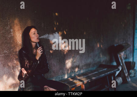 Young woman smoking electronic cigarette while sitting on bench against wall on footpath - Stock Photo