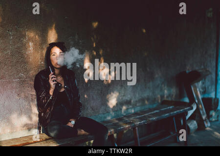 Portrait of confident young woman smoking electronic cigarette while sitting on bench against wall on footpath - Stock Photo