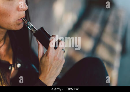 Midsection of young woman smoking electronic cigarette while sitting against wall on footpath - Stock Photo