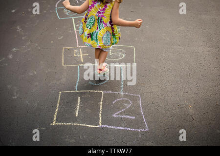 Low section of girl playing hopscotch on road - Stock Photo