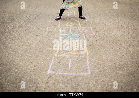 Low section of girl playing hopscotch on street - Stock Photo