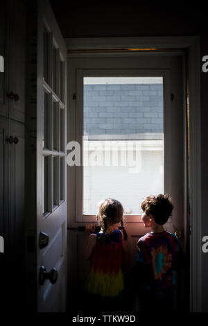 Rear view of siblings looking through window while standing at home - Stock Photo