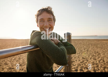 Woman leaning on gymnastic bars at beach against clear sky - Stock Photo