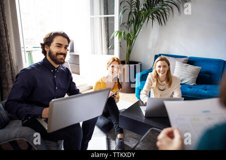 Happy business people looking at colleague during meeting in creative office - Stock Photo