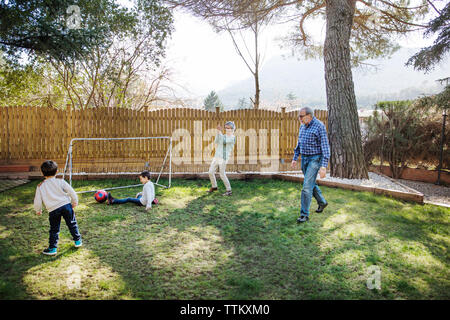 Cheerful grandparents playing soccer with grandsons at yard - Stock Photo