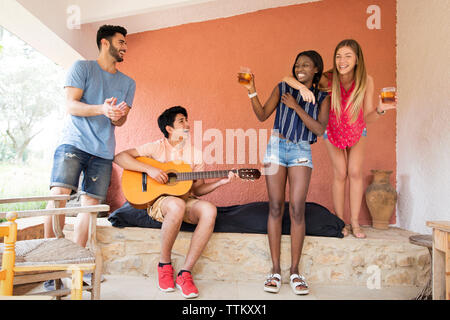 Cheerful women holding iced tea glasses while male friend playing guitar at yard - Stock Photo