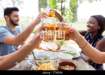 Friends toasting iced tea glasses at outdoor table - Stock Photo