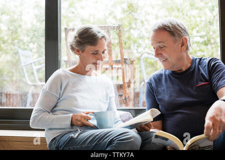 Happy senior couple reading books while sitting by window at home - Stock Photo