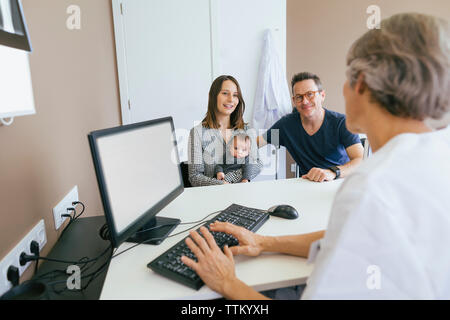 Happy family discussing with doctor at medical clinic - Stock Photo