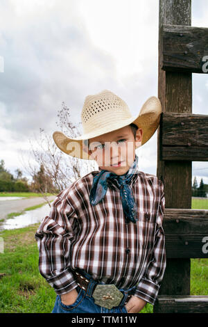 Portrait of cute cowboy standing with hands in pockets on field