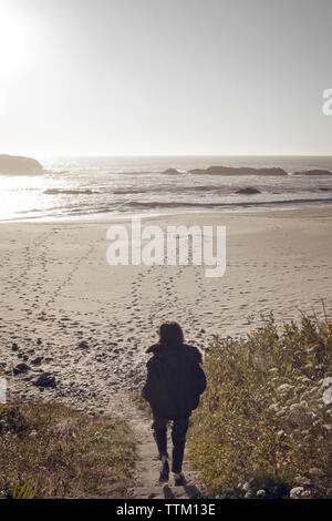 Rear view of woman walking on steps leading towards beach - Stock Photo