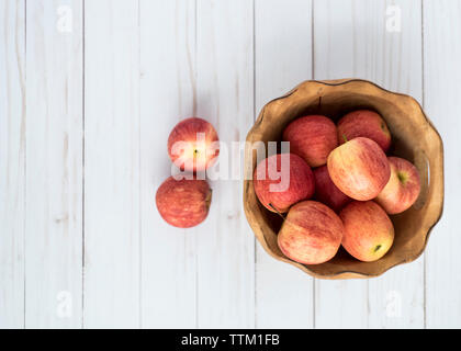 Overhead view of apples wooden bowl on table - Stock Photo