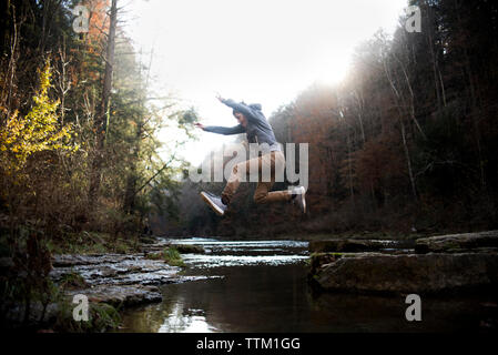 Side view of teenage boy jumping over river against trees in forest