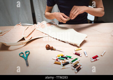 Cropped image of fashion designer stitching fabric at table in workshop - Stock Photo