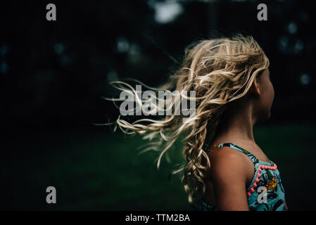 Side view of girl with tousled hair at park - Stock Photo