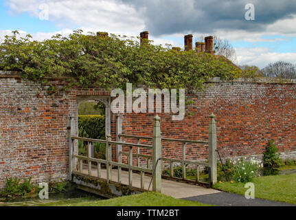 Small wooden bridge with an interesting open pattern crosses a stream and leads into a walled garden.