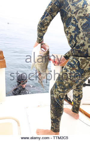 Man in spearfishing suit holding caught fish while friend swimming in sea by boat - Stock Photo