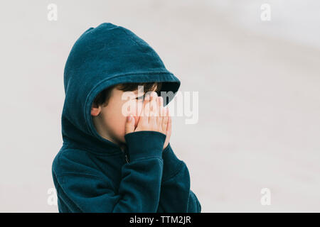 Boy with hands covering mouth standing at beach - Stock Photo