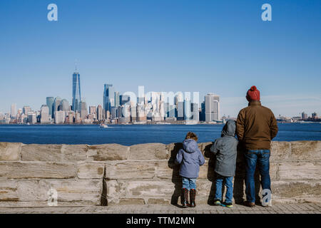 Rear view of father and sons wearing warm clothing looking at cityscape by river against sky - Stock Photo