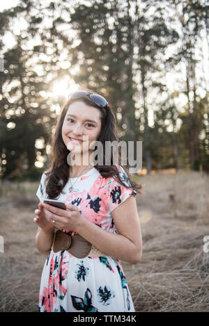 Portrait of smiling young woman using mobile phone while standing against trees in forest - Stock Photo