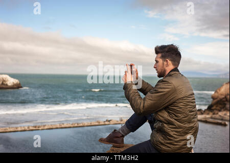 Side view of man photographing sea through smart phone against sky - Stock Photo