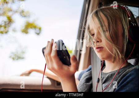 Boy listening to music using mobile phone while sitting in car - Stock Photo