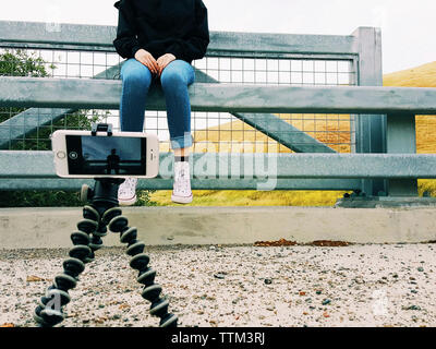 Close-up of mobile phone on tripod photographing teenage girl sitting at railing - Stock Photo