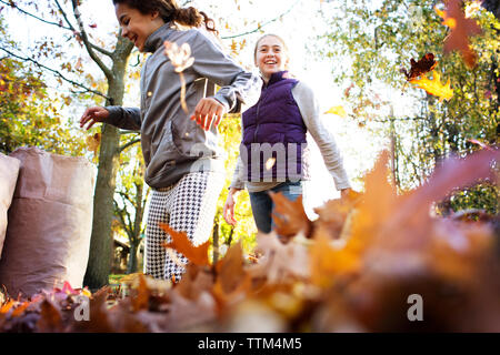 Happy friends playing with autumn leaves on street - Stock Photo