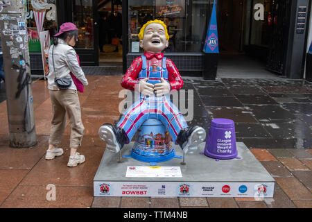 Glasgow, Scotland, UK. 17th June, 2019. Life In Glasgow, created by Taylor McTaggart. This statue shows Oor Wullie dressed in his dungarees, proudly representing the College tartan. His shirt also features the many subjects the College Offers, while his bucket depicts the very best of life in Glasgow. The sculpture is part of Oor Wullie's BIG Bucket Trail. Credit: Skully/Alamy Live News - Stock Photo