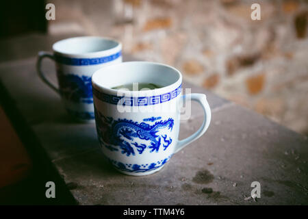 Close-up of tea cups on window sill - Stock Photo