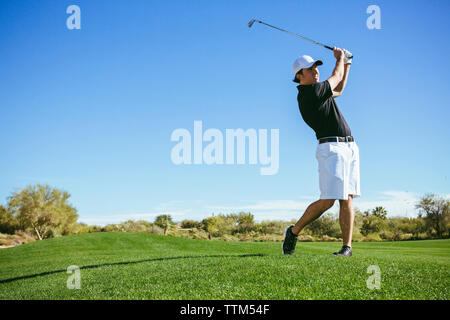 Golfer playing on field against sky - Stock Photo