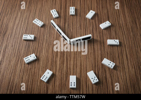 Dominoes in clock shape on wooden table - Stock Photo