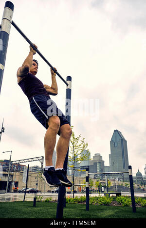Full length of young man practicing pull-ups on gymnastics bar against sky at park in city - Stock Photo