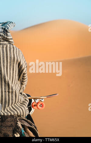 Rear view of man with skateboard sitting on camel during sunny day - Stock Photo