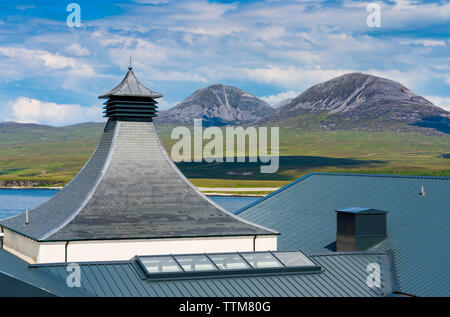 View of new Ardnahoe Distillery on island of Islay with Paps of Jura mountains to rear in Inner Hebrides of Scotland, UK - Stock Photo