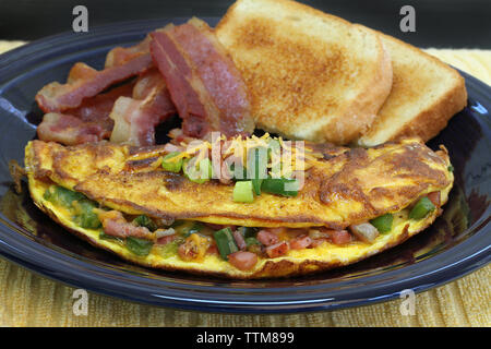 Macro view of a Western or Denver omelet with sides of bacon and toast.  Selective focus on omelet front. - Stock Photo