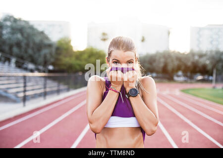 Portrait of sporty woman wiping sweat on face with tank top at field - Stock Photo