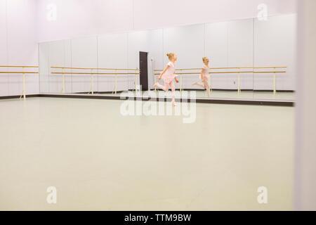 Happy ballet dancer dancing in front of mirror at dance studio - Stock Photo