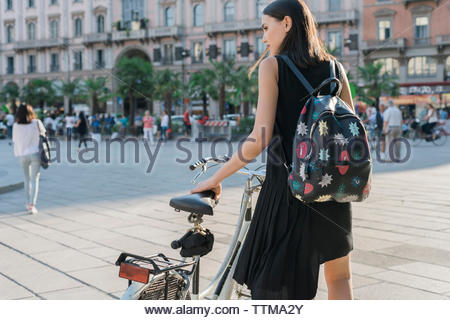 Rear view of woman with bicycle standing on city street - Stock Photo