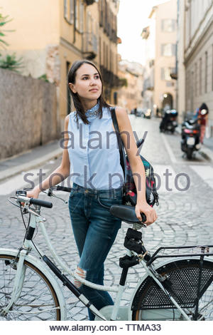 Woman with bicycle looking away while standing on city street - Stock Photo