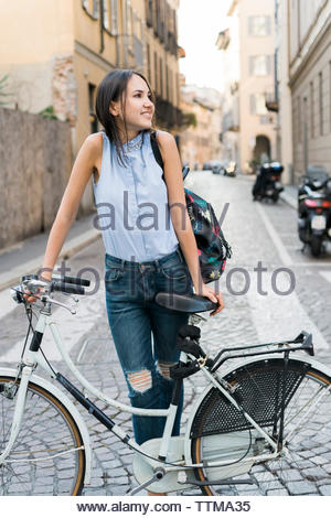 Smiling woman with bicycle standing on city street - Stock Photo