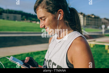 Side view of woman using phone at park - Stock Photo