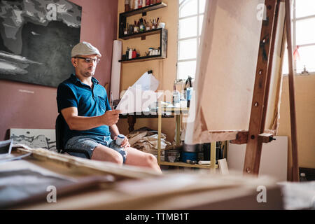 Man working as painter looking at reference image for new painting