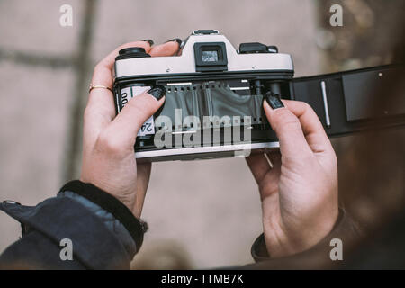 Close-up of woman loading film negative in vintage camera on footpath - Stock Photo